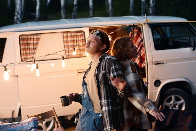Jong koppel samen dansen tijdens kamperen in het bos Premium Foto