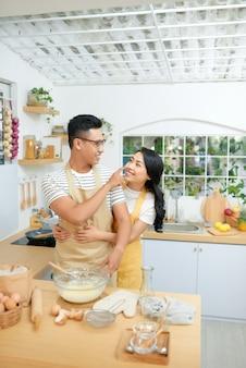 Jong koppel samen deeg maken in de keuken