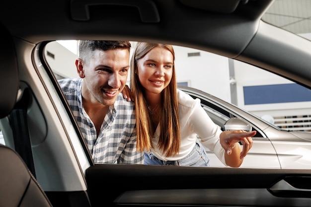 Jong koppel samen kiezen voor hun nieuwe auto in een autowinkel