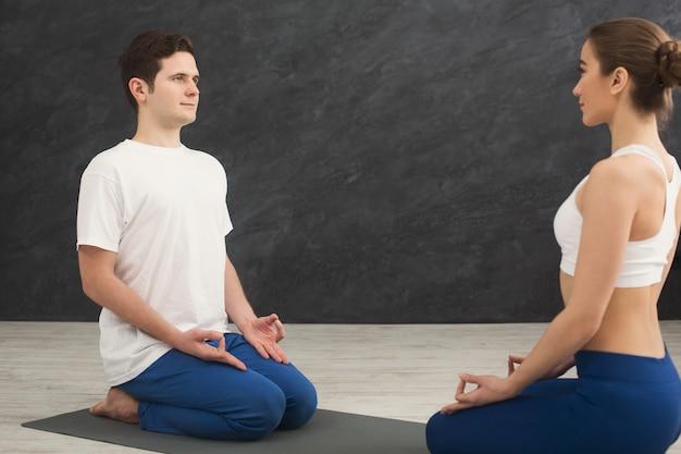 Jong koppel samen mediteren. man en vrouw zitten tegenover elkaar op mat, kopieer ruimte