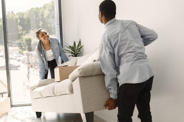Jong koppel samen verhuizen naar nieuw huis. afrikaans amerikaans echtpaar met kartonnen dozen.