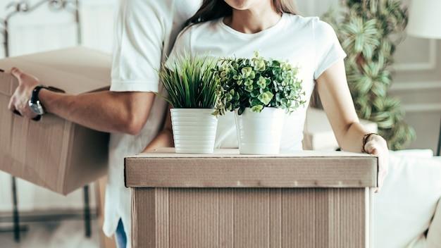 Jong koppel schikken dozen in hun nieuwe appartement close-up