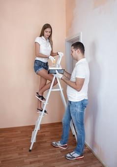 Jong koppel schilderen muur thuis met roller en elkaar helpen ze is op de ladde