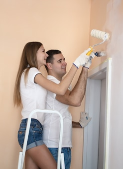 Jong koppel schilderij muur thuis met roller en borstel. meisje staat op de ladder.