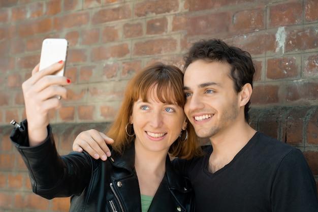 Jong koppel selfie met mobiele telefoon buitenshuis te nemen.