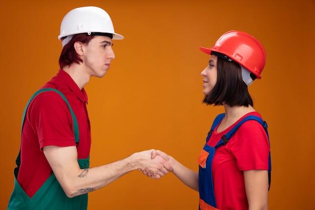 Jong koppel serieuze kerel blij meisje in bouwvakker uniform en veiligheidshelm staande in profielweergave kijken naar elkaar groet geïsoleerd op oranje muur