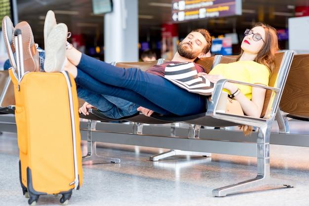 Jong koppel slapen op de stoelen in de wachtkamer van de luchthaven. lang wachten op het vliegtuig