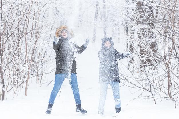 Jong koppel spelen met sneeuw in winter park