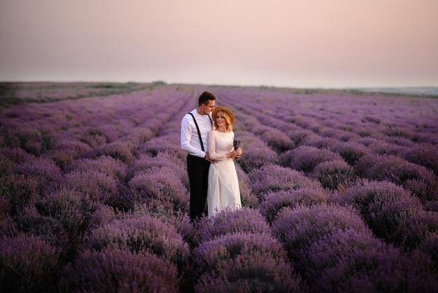 Jong koppel staande in het midden van bloeiende lavendel veld bij zonsopgang