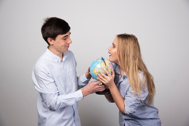 Jong koppel staande met een earth globe op grijze muur