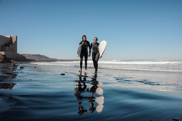 Jong koppel surfers wandelen en lachen langs de kust met zwart zand op zonnige dag