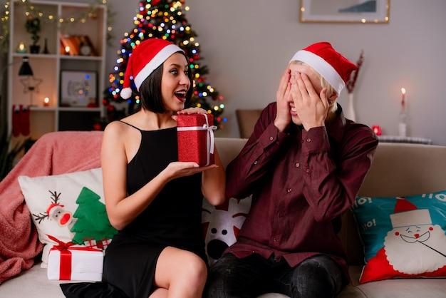 Jong koppel thuis in de kersttijd met kerstmuts zittend op de bank in de woonkamer die geschenken ontvangt