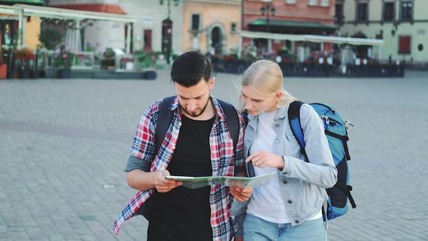 Jong koppel toeristen met kaart lopen en op zoek naar nieuwe historische plek in het stadscentrum. ze lopen en vinden iets interessants.