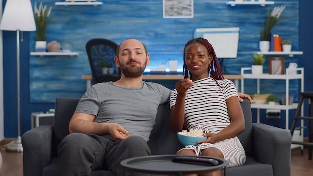 Jong koppel tussen verschillende rassen kijken naar film op tv met popcorn