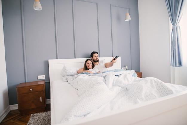 Jong koppel tv kijken terwijl liggend in bed omhelsde.