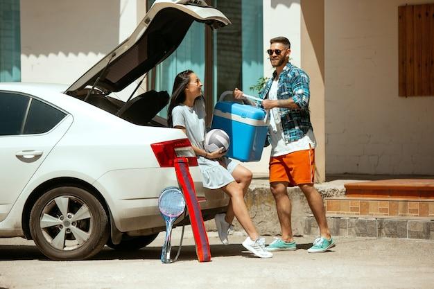 Jong koppel vakantie reis op de auto in zonnige dag voorbereiden. vrouw en man stapelen sportuitrusting. klaar om naar zee, rivier of oceaan te gaan. concept van relatie, zomer, weekend.