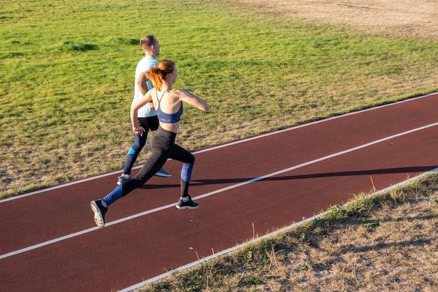 Jong koppel van fitte sporters jongen en meisje lopen terwijl het doen van oefening op rode sporen van openbare stadion buitenshuis.