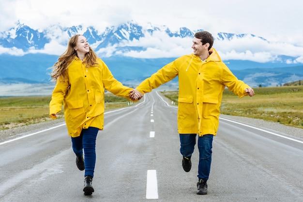 Jong koppel van gelukkige toeristen man en vrouw rennen langs de weg met opgeheven handen