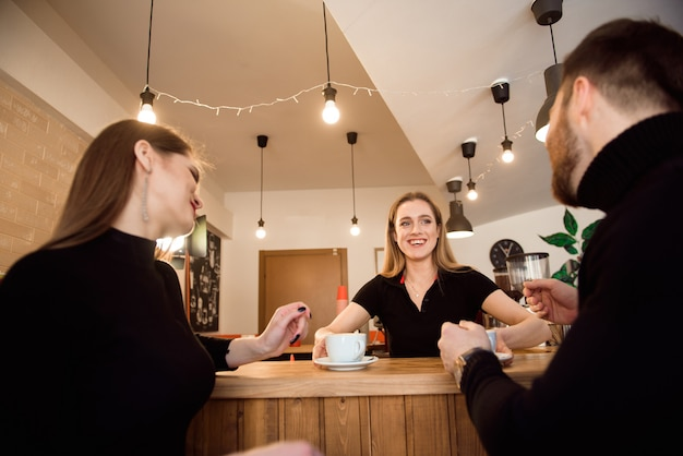 Jong koppel van klanten die koffie van barista in coffeeshop.