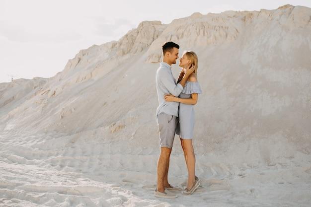Jong koppel van man en vrouw knuffelen buiten in de woestijn.