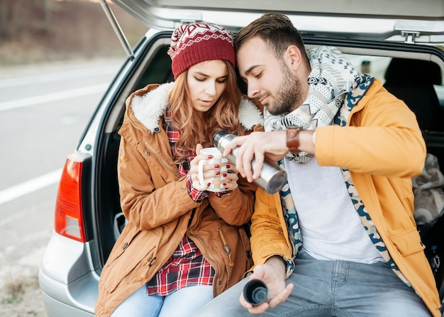 Jong koppel van man en vrouw zittend op de kofferbak van de auto, hete thee drinken op winterdag.