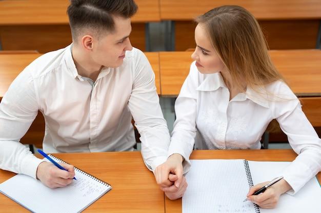 Jong koppel van studenten zitten aan een bureau tijdens een lezing en houden elkaars hand vast