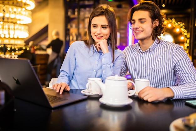 Jong koppel veel plezier tijdens het kijken op laptop in café