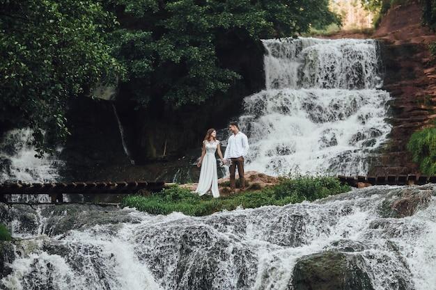 Jong koppel verblijf op berg waterval, gelukkig getrouwde mensen