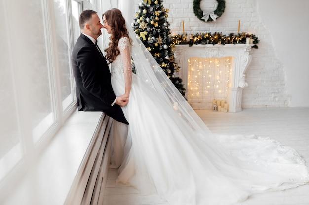 Jong koppel verliefd bruid en bruidegom poseren in studio op achtergrond versierd met kerstboom op hun trouwdag met kerstmis in de buurt van het grote panoramische raam.