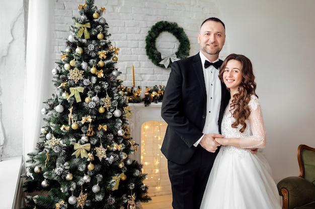 Jong koppel verliefd bruid en bruidegom poseren in studio op achtergrond versierd met kerstboom op hun trouwdag met kerstmis.