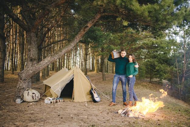 Jong koppel verliefd camping toeristen zitten bij een vuur tegen een tent in het bos luisteren naar retro radio