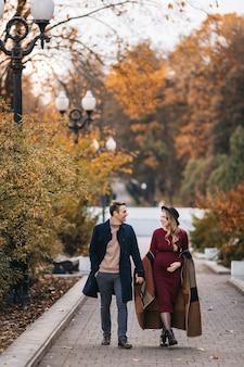 Jong koppel verliefd gelukkige man en zijn zwangere vrouw hand in hand en wandelen door een park op een s...