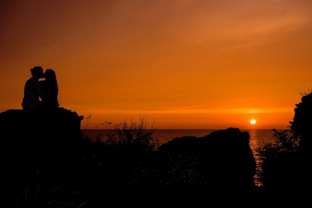 Jong koppel verliefd genieten van de prachtige zonsondergang op het strand