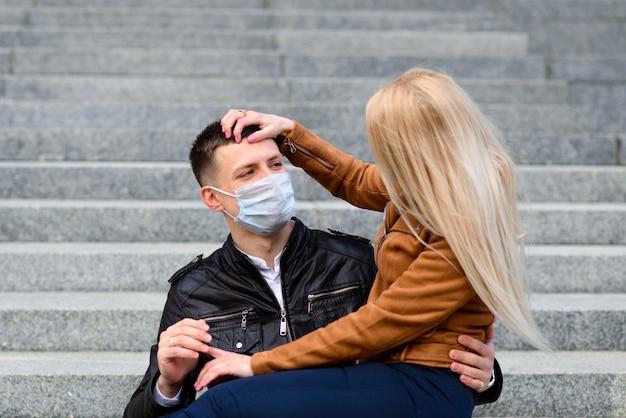Jong koppel verliefd in beschermende medische masker op gezicht buiten op straat. milieuvervuiling concept. jongen en meisje in virusbescherming