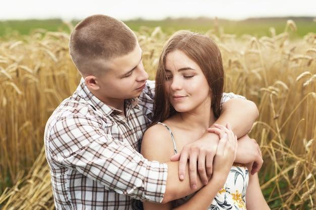 Jong koppel verliefd in een tarweveld man en meisje knuffelen in de natuur