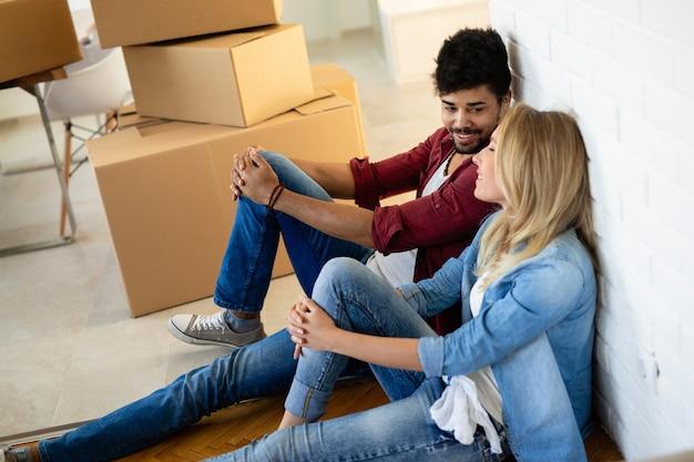 Jong koppel verliefd kartonnen dozen uitpakken in nieuw huis verhuizen in concept