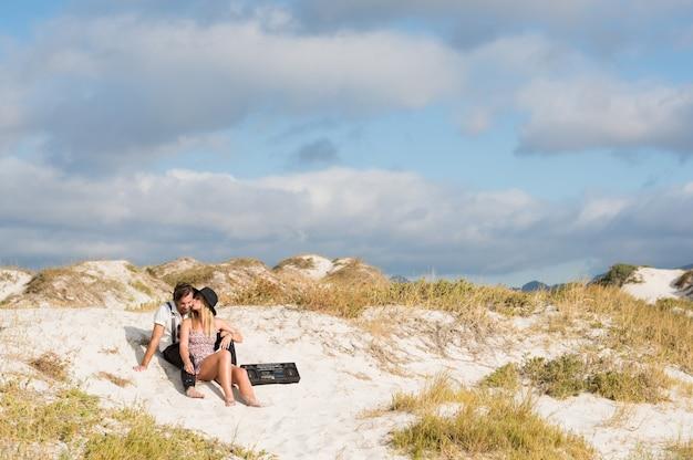 Jong koppel verliefd op het strand zitten en luisteren naar muziek met vintage radio