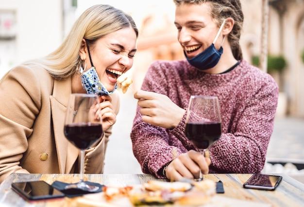 Jong koppel verliefd op open gezichtsmaskers met plezier in wijnbar buiten