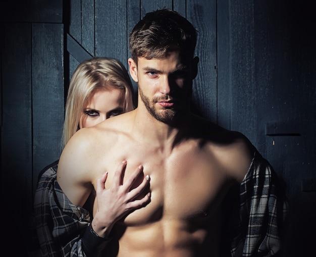 Jong koppel verliefd sensuele paar blonde vrouw en naakte gespierde man met blote torso sexy lichaam dicht bij elkaar in studio op houten