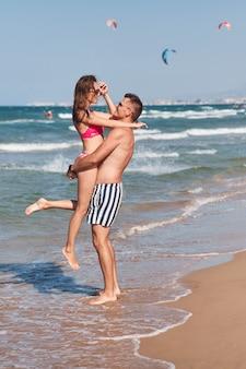 Jong koppel verliefd wandelen op het strand.