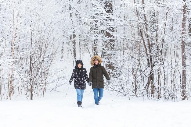 Jong koppel verliefd wandelingen in het besneeuwde bos. actieve wintervakantie.