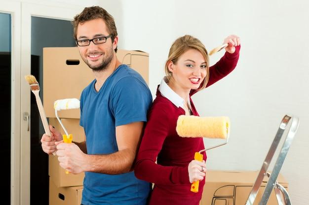 Jong koppel verplaatsen in een huis of appartement, ze schilderen en doen renovatiewerkzaamheden