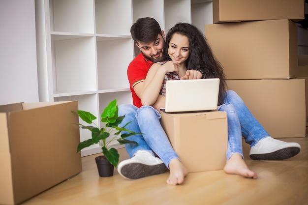 Jong koppel verplaatsen in een nieuw huis, zitten en ontspannen na het uitpakken, op zoek naar iets op laptop