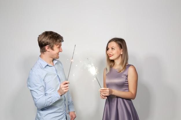 Jong koppel vieren hun verjaardag met wonderkaarsen op witte muur