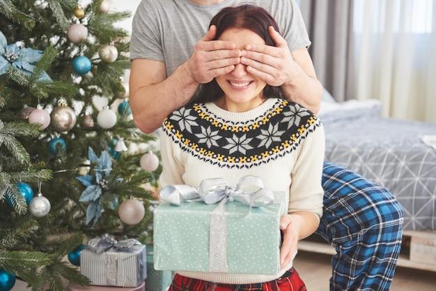 Jong koppel vieren kerstmis. een man presenteerde plotseling een cadeau aan zijn vrouw. het concept van gezinsgeluk en welzijn