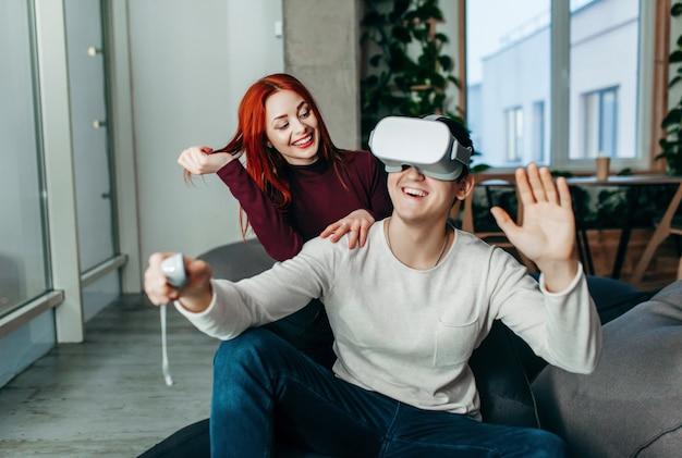 Jong koppel virtuele realiteit (vr) ervaren in de woonkamer