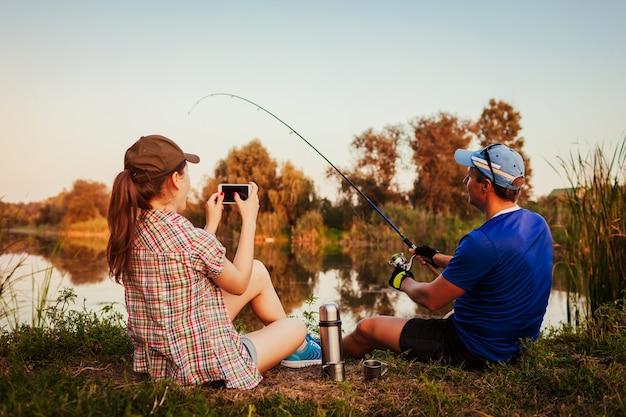 Jong koppel vissen en thee drinken op de rivier bij zonsondergang