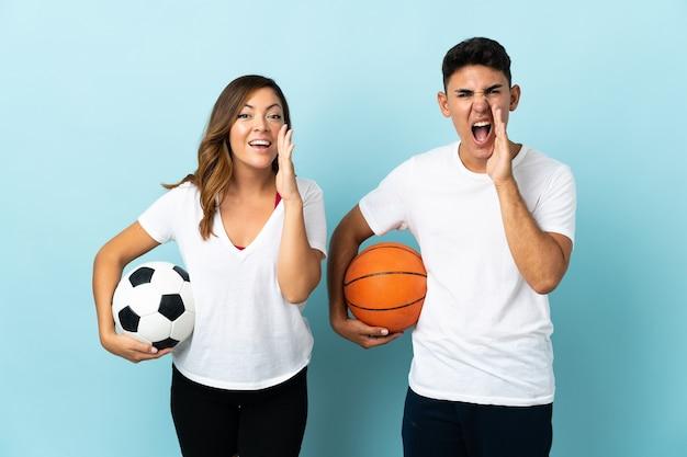 Jong koppel voetballen en basketballen op blauw schreeuwen en iets aankondigen