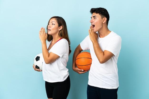 Jong koppel voetballen en basketballen op blauw schreeuwen met mond wijd open voor de laterale