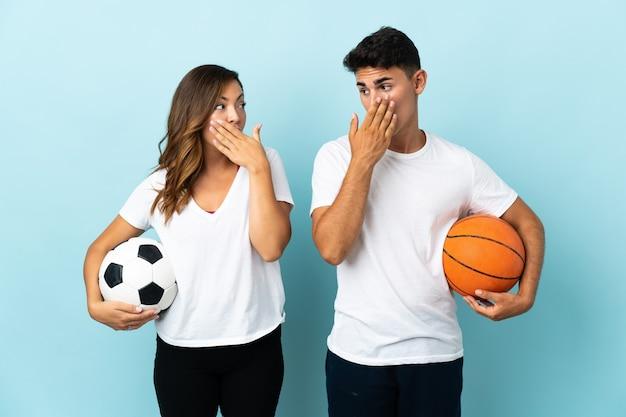 Jong koppel voetballen en basketballen op blauwe bedekkende mond met handen voor iets ongepasts te zeggen